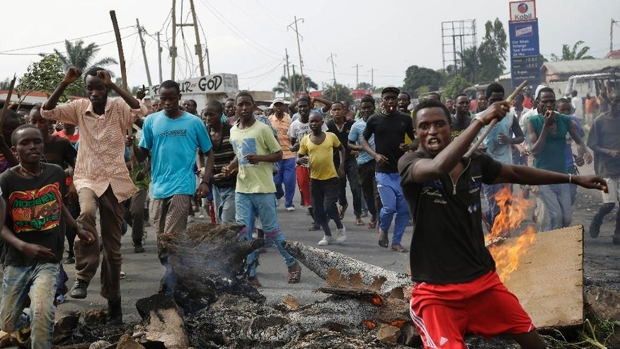 Demonstrators rally past a barricade in the Cibitoke neighborhood of Bujumbura, Burundi, Tuesday, May 19, 2015. A climate of fear has engulfed in Burundi's capital, as President Pierre Nkurunziza's government cracks down on the people suspected to have been involved in an attempted coup a week ago.  (AP Photo/Jerome Delay)