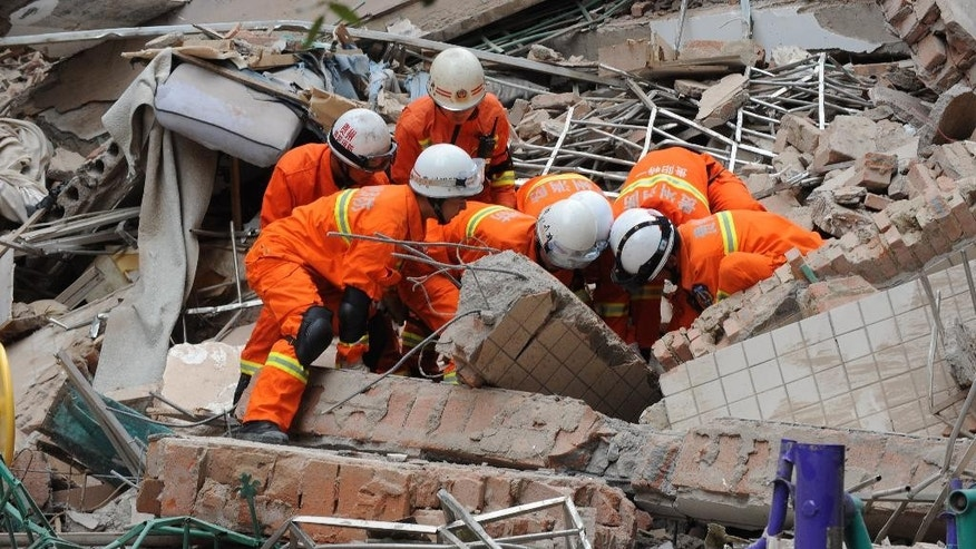Rescuers work amid the debris of a collapsed nine-story residential building in Guiyang in southwestern China's Guizhou province Wednesday, May 20, 2015. The building collapsed following a landslide triggered by heavy rainfall on Wednesday, trapping at least several people, the city government said. (Chinatopix Via AP) CHINA OUT