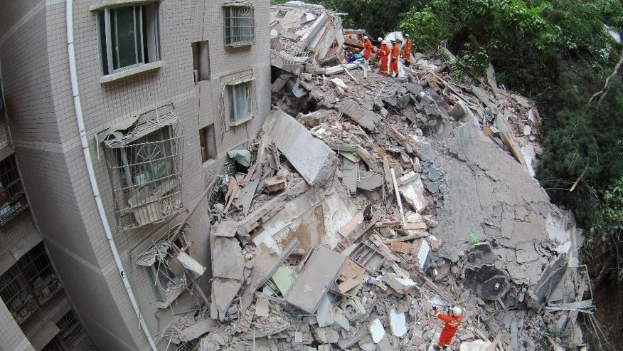 In this photo taken with a fisheye lens, rescuers work amid the debris of a collapsed nine-story residential building in Guiyang in southwestern China's Guizhou province Wednesday, May 20, 2015. The building collapsed following a landslide on Wednesday, trapping at least several people, the city government said. (Chinatopix Via AP) CHINA OUT