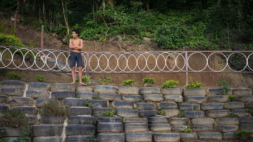 In this May 7, 2015 photo, a boy stands on top of tires that form a crescent-shaped amphitheater, backdropped by old bicycle wheels serving as railings, in Sitie Park in Vidigal, a shantytown on the hills of Rio de Janeiro, Brazil. The leafy green sanctuary was once a dumping ground for anything from broken washing machines to the remains of deceased dogs. (AP Photo/Felipe Dana)