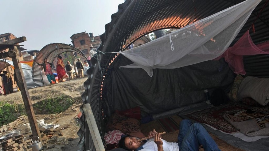 A Nepalese man, whose house was damaged in the April 25 earthquake, plays a flute in a temporary shelter made out of galvanized sheet in Bhaktapur, Nepal, Tuesday, May 19, 2015. Nepal is facing billions in reconstruction costs with almost 745,600 buildings and homes damaged or destroyed, including at least 87,700 in the capital, according to Nepal's emergency authority. (AP Photo/Niranjan Shrestha)