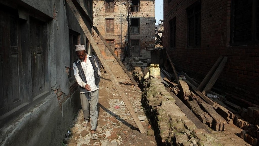 A Nepalese walks past a damaged house supported by wooden beams in Bhaktapur, Nepal, Tuesday, May 19, 2015. Nepal is facing billions in reconstruction costs with almost 745,600 buildings and homes damaged or destroyed, including at least 87,700 in the capital, according to Nepal's emergency authority. (AP Photo/Niranjan Shrestha)