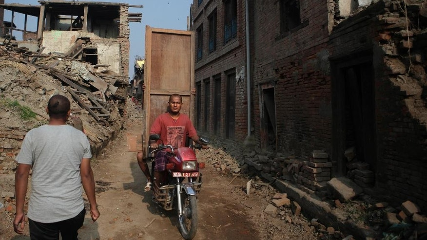 A Nepalese man carries belongings salvaged from his house that was damaged in the April 25 earthquake in Bhaktapur, Nepal, Tuesday, May 19, 2015. Nepal is facing billions in reconstruction costs with almost 745,600 buildings and homes damaged or destroyed, including at least 87,700 in the capital, according to Nepal's emergency authority. (AP Photo/Niranjan Shrestha)