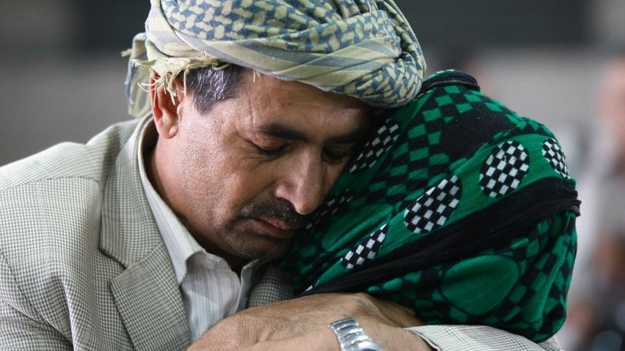 A Yemeni man hugs his mother, who was stranded in Egypt after conflict broke out in Yemen, after she arrived at Sanaa airport, Yemen, Wednesday, May 20, 2015. The airport was opened temporarily as two planes, one from  India and one from Egypt, arrived carrying more than 300 Yemeni. (AP Photo/Hani Mohammed)