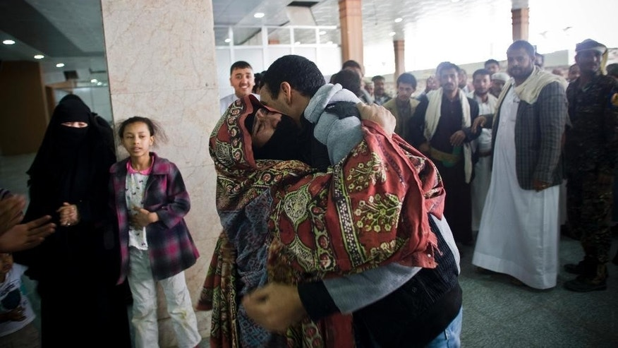 A Yemeni man hugs his mother, who was stranded in Egypt after conflict broke out in Yemen, after arriving at Sanaa airport, Yemen, Wednesday, May 20, 2015. The airport was opened temporarily as two planes, one from  India and one from Egypt, arrived carrying more than 300 Yemeni. (AP Photo/Hani Mohammed)