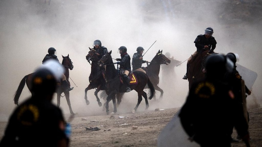 Mounted riot police clash with squatters during a land eviction in Lima Peru, Tuesday, May 19, 2015. On Monday hundreds of people squatted on land that according to the Ministry of Culture is an archaeological site. (AP Photo/Rodrigo Abd)