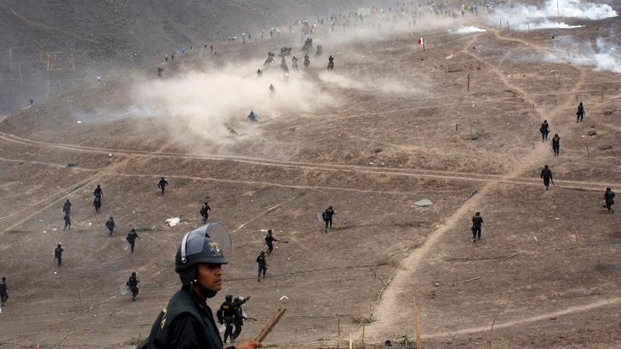 Riot police clash with squatters during a land eviction in Lima Peru, Tuesday, May 19, 2015. On Monday hundreds of people squatted on land that according to the Ministry of Culture is an archaeological site. (AP Photo/Rodrigo Abd)
