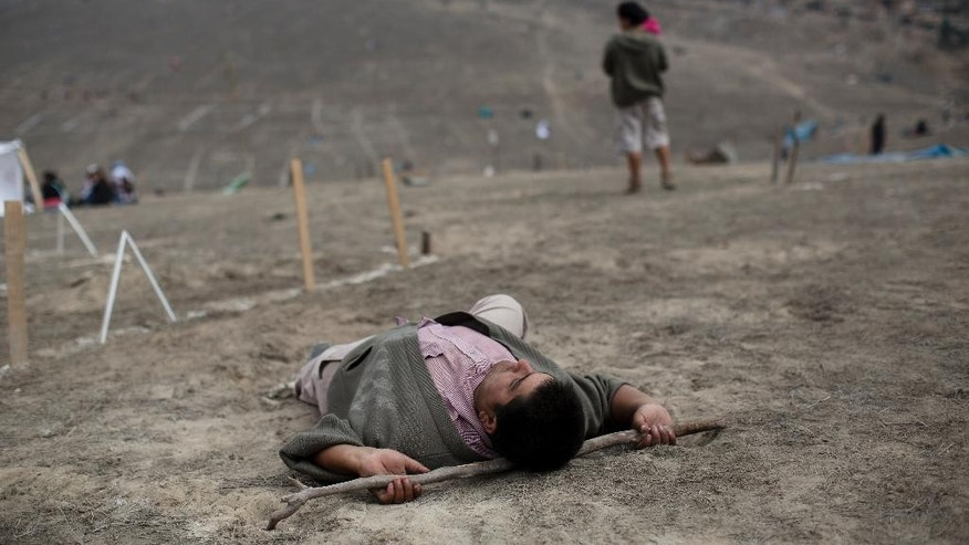 A man rests on the ground with a stick before a land eviction in Lima Peru, Tuesday, May 19, 2015. On Monday hundreds of people squatted on land that according to the Ministry of Culture is an archaeological site. (AP Photo/Rodrigo Abd)