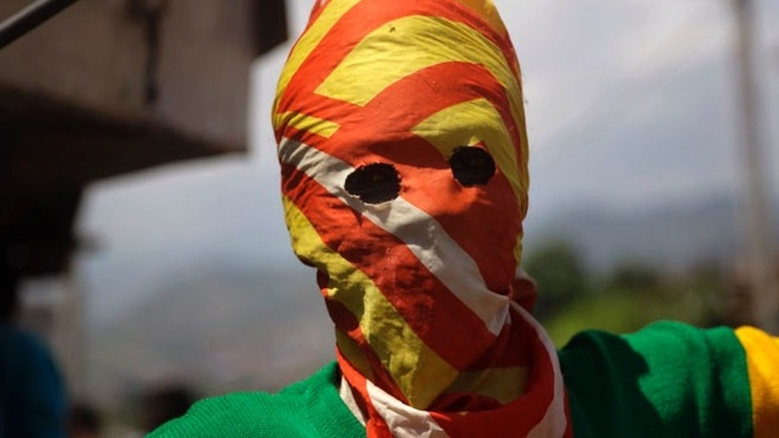 May 21, 2015: A masked Protester waits for  police during clashes in the Nyakabyga neighborhood of Bujumbura, Burundi. (AP)