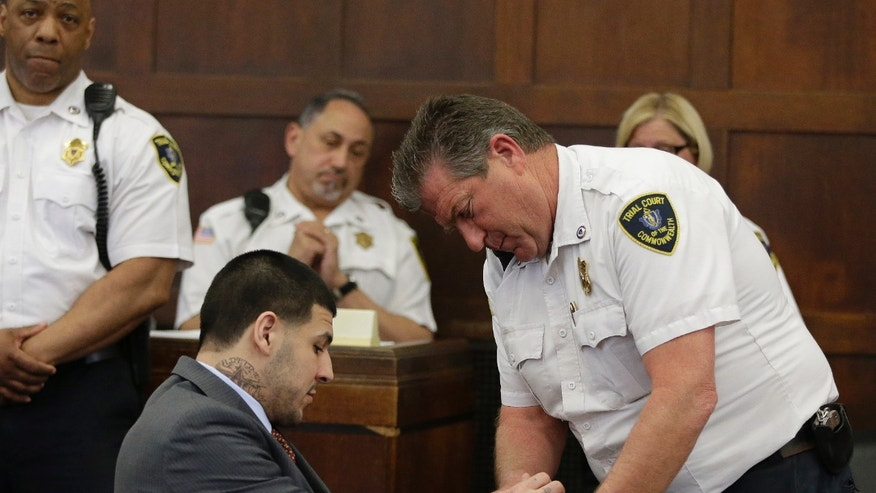 Hernandez has his handcuffs removed at Suffolk Superior Court, Thursday, May 21, 2015, in Boston.
