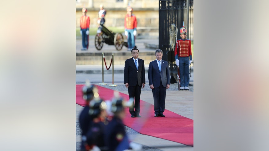 China's Premier Li Keqiang, left, and Colombia's President Juan Manuel Santos, right, receive military honors before they review the troops during a welcoming ceremony at the Presidential Palace in Bogota, Colombia, Thursday, May 21, 2015. Li Keqiang is in Colombia in an official two-day visit and will then tour Peru and Chile. (AP Photo/Fernando Vergara)