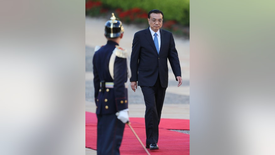 China's Premier Li Keqiang, right, reviews troops during a welcoming ceremony at the Presidential Palace in Bogota, Colombia, Thursday, May 21, 2015. Li Keqiang is in Colombia in an official two-day visit and will then tour Peru and Chile. (AP Photo/Fernando Vergara)
