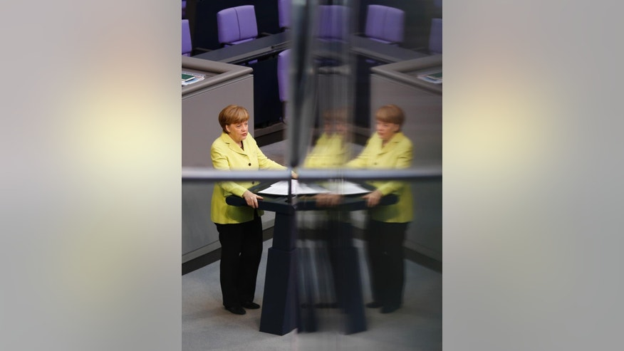 German Chancellor Angela Merkel is reflected in a window pane as she delivers a government declaration about the European Union and an Eastern Partnership with former Soviet Republics at the German parliament Bundestag, in Berlin, Germany, Thursday, May 21, 2015. Merkel will attend a summit of the European Union and former Soviet Republics in Latvia's capital Riga in the afternoon.  (AP Photo/Markus Schreiber)