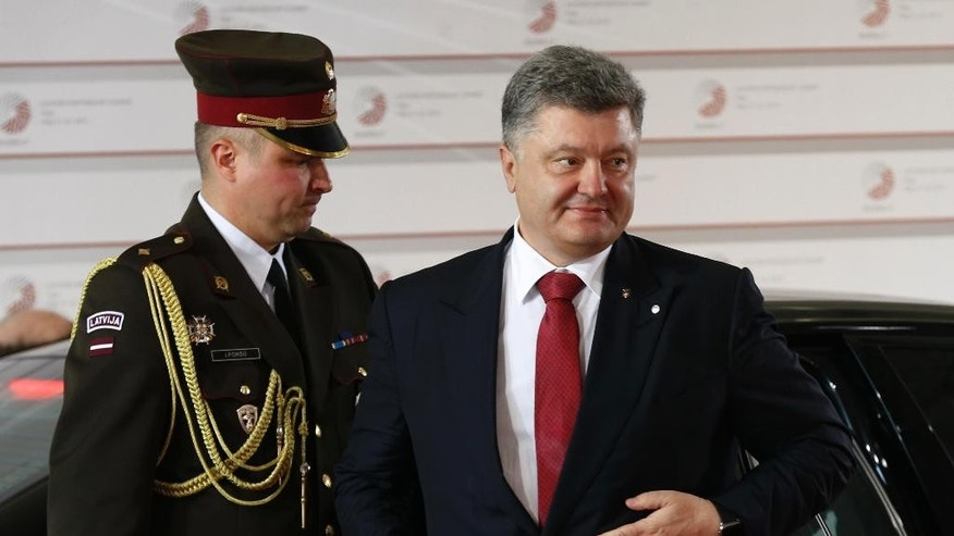 Ukrainian President Petro Poroshenko, right, arrives for a formal dinner at the Eastern Partnership summit in Riga, on Thursday, May 21, 2015. EU leaders on Thursday will seek new ways to bolster ties with six post-communist nations in Eastern Europe, a year and a half after a previous summit of the Eastern Partnership ended with a fateful standoff over Ukraine. (AP Photo/Mindaugas Kulbis)