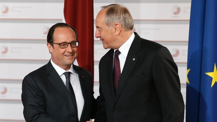 French President Francois Hollande, left, is greeted by Latvian President Andris Berzins as he arrives for a formal dinner at the Eastern Partnership summit in Riga, on Thursday, May 21, 2015. EU leaders on Thursday will seek new ways to bolster ties with six post-communist nations in Eastern Europe, a year and a half after a previous summit of the Eastern Partnership ended with a fateful standoff over Ukraine. (AP Photo/Mindaugas Kulbis)