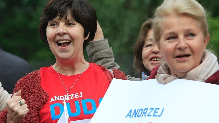 Supporters of  Andrzej Duda react in front of a tv studio during the second debate between opposition candidate Andrzej Duda,  and incumbent Bronislaw Komorowski ahead of the May 24 presidential runoff  in Warsaw, Poland, Thursday, May 21, 2015.(AP Photo/Czarek Sokolowski)