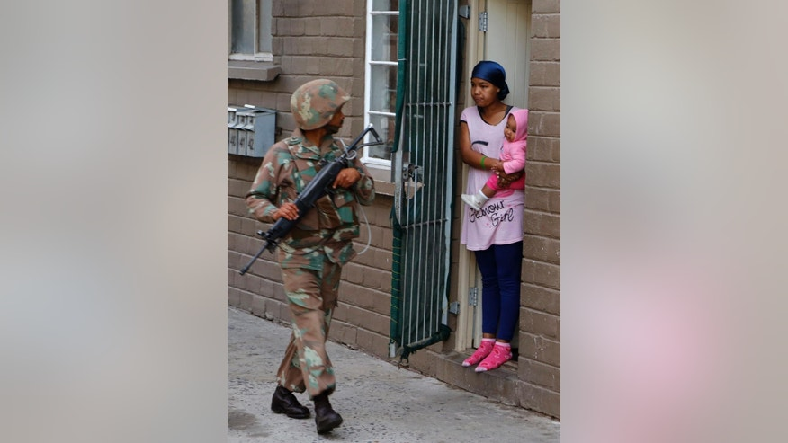 A South African soldier walks past a woman holding her baby standing at the entrance of her flat in Manenberg, South Africa Thursday, May 21, 2015. Hundreds of South African police and army members took part in an early morning raid on Manenberg after recent gang violence, looking for drugs and illegal firearms. (AP Photo/Schalk van Zuydam)