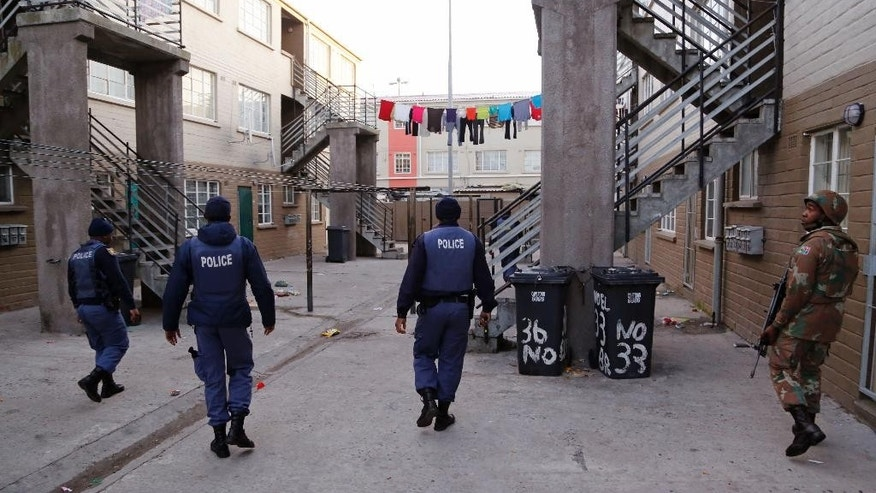 A South African soldier, right,  provide security for  policemen, left,  as they look for drugs in  Manenberg, South Africa,  Thursday, May 21, 2015. Hundreds of South African Police and Army members took part in an early morning raid on Manenberg after recent gang violence, looking fro drugs and illegal firearms.  (AP Photo/Schalk van Zuydam)
