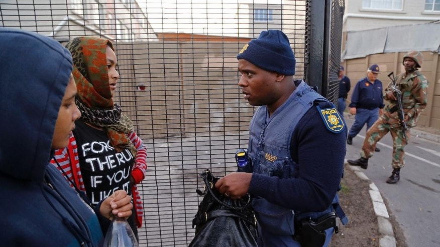 A South African policeman, right, speaks to woman as he and others search for drugs  in Manenberg, South Africa,  Thursday, May 21, 2015. Hundreds of South African Police and Army members took part in an early morning raid on Manenberg after recent gang violence, looking fro drugs and illegal firearms.  (AP Photo/Schalk van Zuydam)