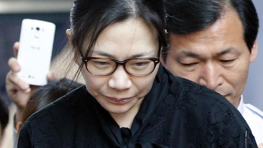 Former Korean Air executive Cho Hyun-ah, center, leaves the Seoul High Court in Seoul, South Korea, Friday, May 22, 2015. The upper court Friday sentenced Cho to 10 months in prison and then suspended the sentence for two years. (AP Photo/Lee Jin-man)