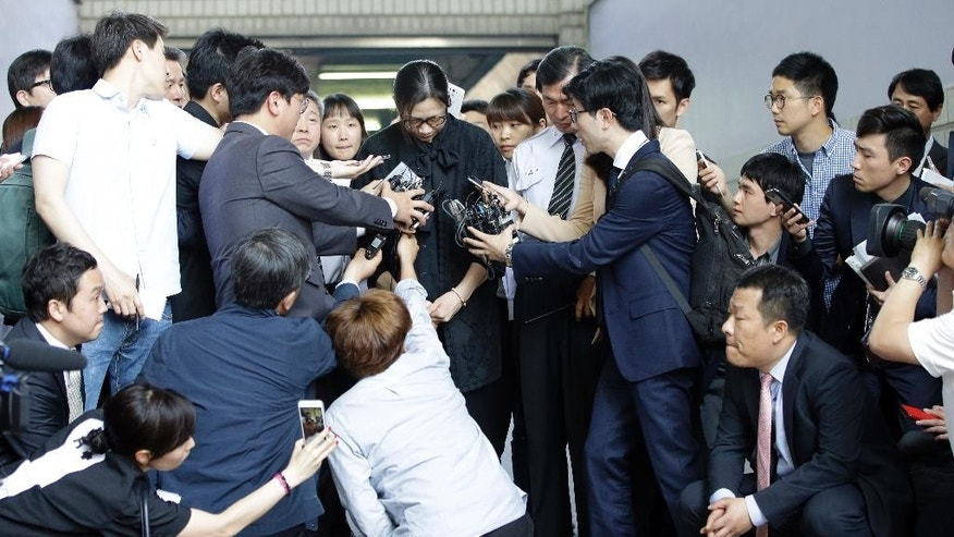 Former Korean Air executive Cho Hyun-ah, center, is surrounded by reporters at the Seoul High Court in Seoul, South Korea, Friday, May 22, 2015. The upper court Friday sentenced Cho to 10 months in prison and then suspended the sentence for two years. (AP Photo/Lee Jin-man)
