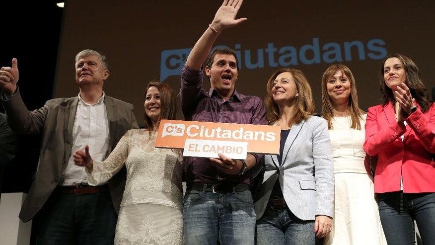 In this May 16, 2015 photo, the leader of Ciudadanos Party (Citizens), Albert Rivera, center, waves to his supporters during a rally for upcoming local elections in Barcelona, Spain. Nearly a decade ago, Rivera caused a stir in Spanish local politics by posing nude in campaign posters. These days, he sports Hugo Boss suits but his campaign on the national stage is no less eye-catching: His upstart Citizens Party is cutting into support for the ruling conservatives, threatening to bust open Spain's traditional two-party system. (AP Photo/Manu Fernandez)