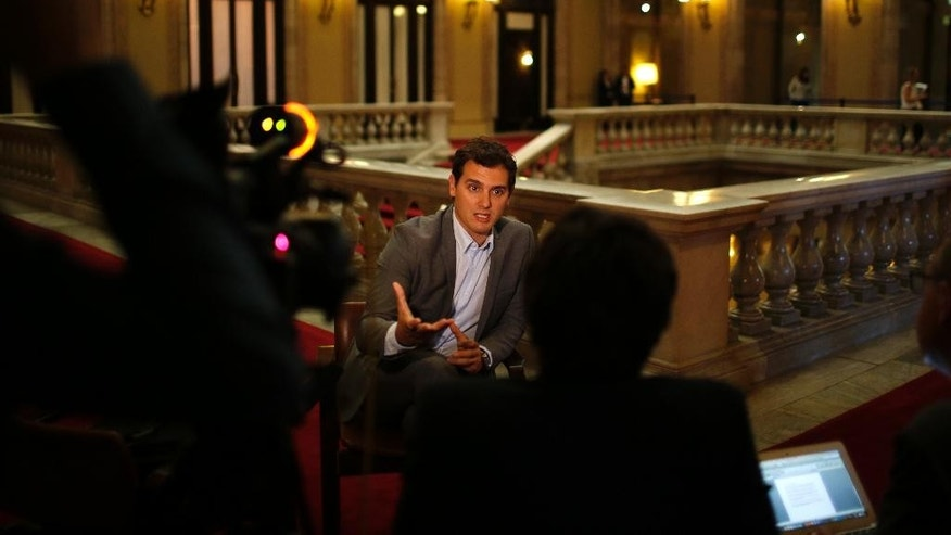 In this May 6, 2015 photo, the leader of Ciudadanos Party (Citizens), Albert Rivera, responds to a question during an interview for The Associated Press in the Catalonia Parliament in Barcelona, Spain. Nearly a decade ago, Rivera caused a stir in Spanish local politics by posing nude in campaign posters. These days, he sports Hugo Boss suits but his campaign on the national stage is no less eye-catching: His upstart Citizens Party is cutting into support for the ruling conservatives, threatening to bust open Spain's traditional two-party system. (AP Photo/Emilio Morenatti)