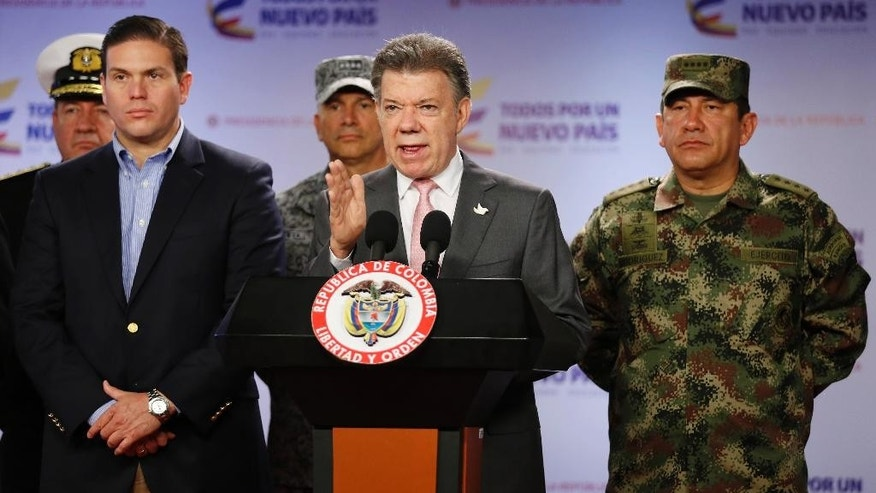 Colombia's President Juan Manuel Santos announces that at least 26 leftist rebels have been killed in a raid in western Colombia, as he's flanked by Defense Minister Juan Carlos Pinzon, left, and Armed Forces Commander Gen. Juan Pablo Rodriguez, at the presidential palace in Bogota, Friday, May 22, 2015. Colombia's largest rebel group, the Revolutionary Armed Forces of Colombia (FARC), announced they're ending a unilateral cease-fire in response to the military raid on their guerrilla camp. (AP Photo/Fernando Vergara)