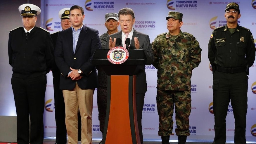 Colombia's President Juan Manuel Santos announces that at least 26 leftist rebels have been killed in a raid in western Colombia, as he's accompanied by Navy Commander Adm. Hernando Wills, left, Defense Minister Juan Carlos Pinzon, second from left, Armed Forces Commander Gen. Juan Pablo Rodriguez, second from right, and National Police Chief Gen. Rodolfo Palomino, right, at the presidential palace in Bogota, Friday, May 22, 2015.  Colombia's largest rebel group, the Revolutionary Armed Forces of Colombia (FARC), announced they're ending a unilateral cease-fire in response to the military raid on their guerrilla camp. (AP Photo/Fernando Vergara)