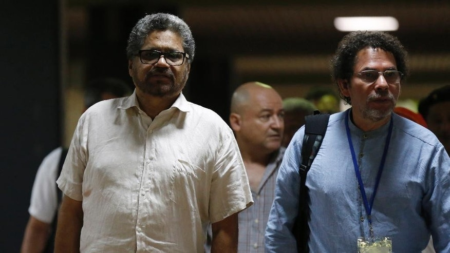 Ivan Marquez, chief negotiator for the Revolutionary Armed Forces of Colombia, left, arrives for a new round of peace talks with Colombia's government, accompanied by fellow FARC delegates Pastor Alape, right, and Carlos Antonio Lozada, center back, in Havana, Cuba, Thursday, May 21, 2015. (AP Photo/Desmond Boylan)