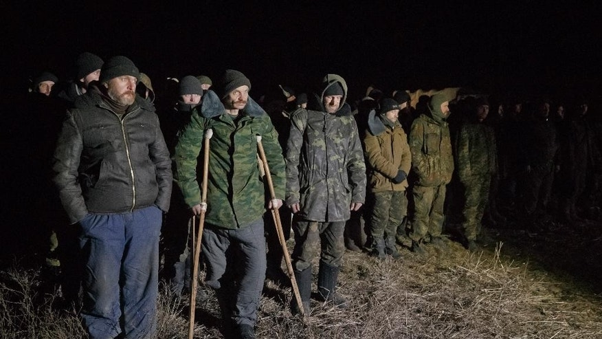 FILE - In this Saturday Feb. 21, 2015 file photo, Ukrainian prisoners of war wait in line before a prisoner exchange in Russia-backed separatist controlled territory, near the village of Zholobok, some 20 kilometers (12 miles) west of Luhansk, Ukraine. Both warring sides in eastern Ukraine are perpetrating war crimes almost daily, including torturing prisoners and summarily killing them, the Amnesty International rights group said in a report Friday May 22, 2015. (AP Photo/Vadim Ghirda, file)