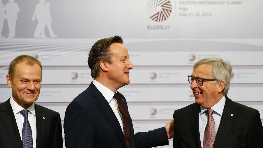 European Commission President Jean-Claude Juncker, right, speaks with British Prime Minister David Cameron, center, during arrivals at the Eastern Partnership summit in Riga, on Friday, May 22, 2015. EU leaders gather for a second day of meetings with six post-communist nations to discuss various issues, including enlargement, the economy and Ukraine. At left is European Council President Donald Tusk. (AP Photo/Mindaugas Kulbis)