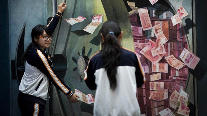 A woman takes a souvenir photo for her friend posing with a 3-D painting of a vault loaded with piles of 100 Chinese yuan (US$16.17) notes at a shopping mall in Beijing, China Friday, May 22, 2015. Negotiators from 57 governments completed work Friday on a charter for a Chinese-led Asian regional bank and it is due to be signed in late June, the Chinese finance ministry said. (AP Photo/Andy Wong)