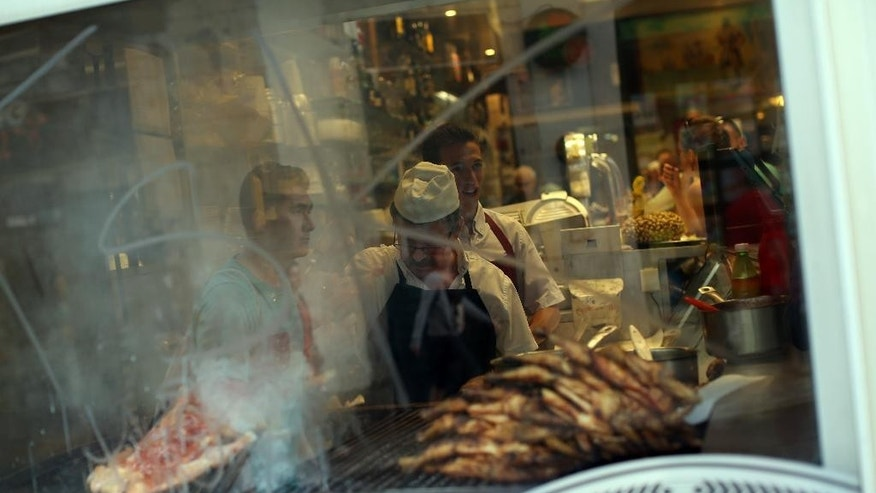 "A man grills meat in a barbecue of a Portuguese traditional food restaurant in Lisbon, Thursday, May 21, 2015. European Central Bank head Mario Draghi said that ""growth is too low everywhere"" in Europe despite a modest recovery, during an ECB's conference on inflation and unemployment in Sintra, Portugal. (AP Photo/Francisco Seco)"