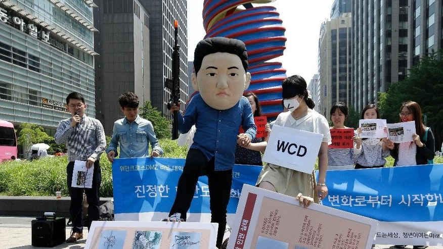 May 22, 2015 - A South Korean university student, center left, wearing a mask of North Korean leader Kim Jong Un, with his fellow student symbolizing the women activists of WCD, Women Cross DMZ, during a gathering to oppose the group's plans to march from North Korea to South Korea across the demilitarized zone, in Seoul, South Korea.