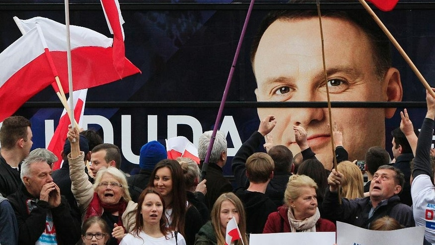Supporters of  Andrzej Duda react in front of a tv studio during the second debate between opposition candidate Andrzej Duda,  and incumbent Bronislaw Komorowski ahead of the May 24 presidential runoff  in Warsaw, Poland, Thursday, May 21, 2015. (AP Photo / Czarek Sokolowski)