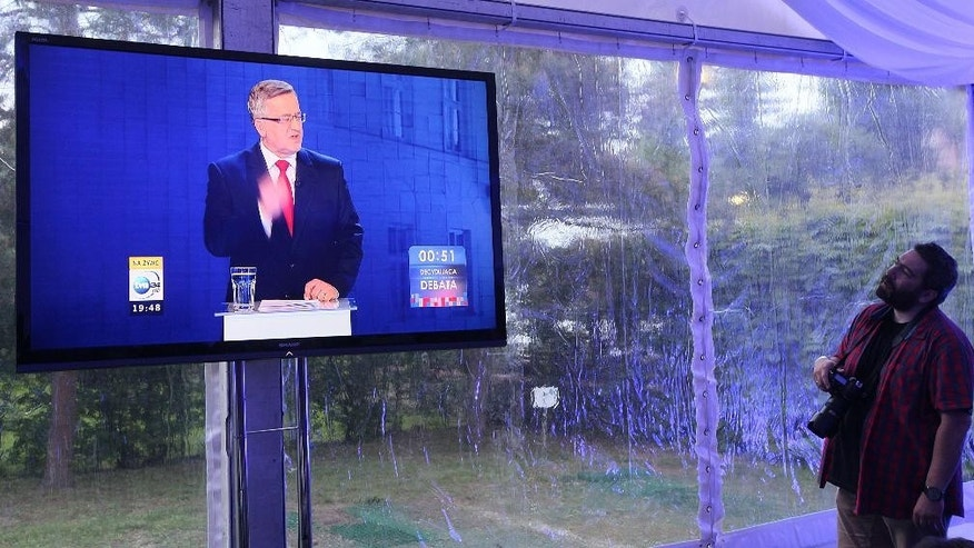 A journalist watches on a video screen incumbent Bronislaw Komorowski discuss the  second election tv debate ahead of the May 24 presidential runoff  in Warsaw, Poland, Thursday, May 21, 2015. (AP Photo/Czarek Sokolowski)