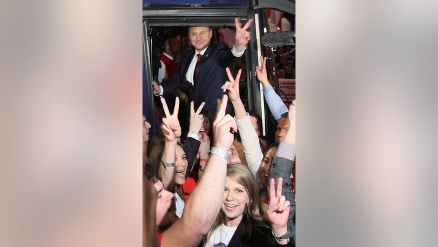 Presidential candidate for main right wing party Law and Justice Andrzej Duda, top, makes a V-victory sign as he greets supporters after the second presidential debate with Polish President and presidential candidate Bronislaw Komorowski, not pictured, at the headquarters of TVN24 television channels, in Warsaw, Poland, Thursday, May 21, 2015.(AP Photo/Czarek Sokolowski)