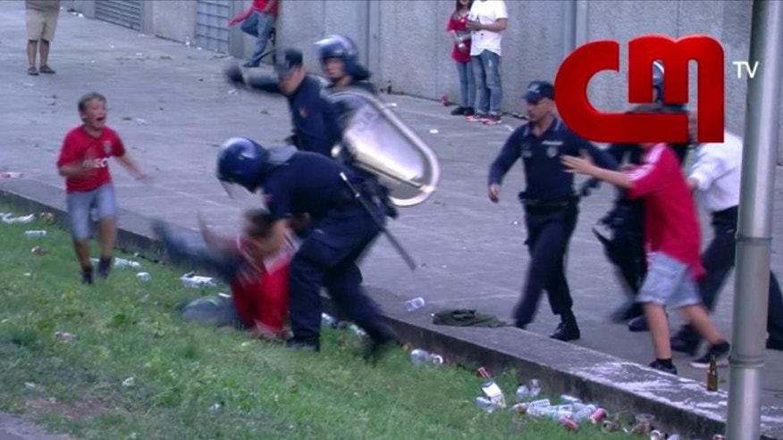 In this screen grab made from video provided by CMTV, a boy cries as his father is attacked by police with batons, outside of a stadium, in Lisbon, Portugal, late Monday, May 18, 2015. Portuguese prosecutors are investigating a policeman who beat a man in front of his young children and punched their grandfather outside a soccer stadium, sparking a national scandal. Police approached Jose Magalhaes, his two sons and his father Sunday outside Guimaraes stadium in northern Portugal, where Benfica had just won the Portuguese league title, according to film footage and witness reports. (CMTV via AP)