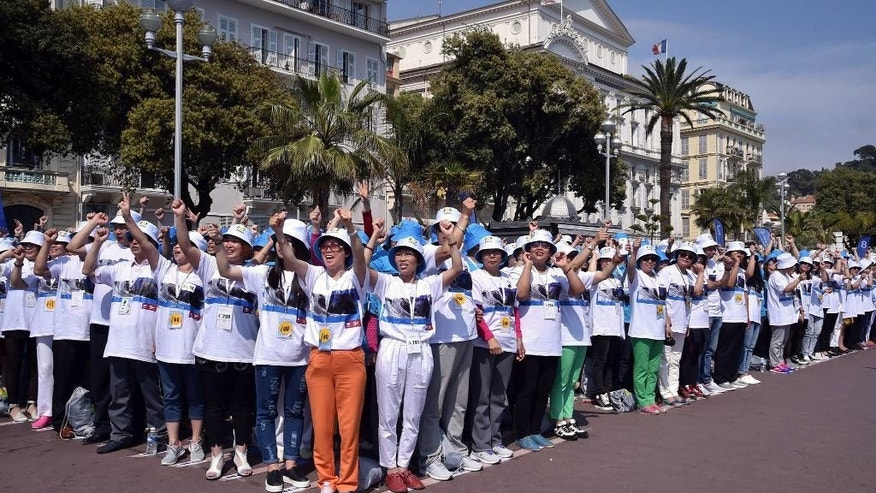 FILE - In this May 8, 2015 file photo, employees of the Tiens Group, a Chinese company which sells medicinal products, including via direct marketing, cheer as they attend a parade organized by CEO Li Jinyuan as part of a four-day celebration weekend for the 20th anniversary of his company, on the Promenade des Anglais, Nice, southeastern France. All-expenses-paid trips to reward top earners aren't unusual, but Chinese direct-sales companies are taking it to an extreme by sending thousands abroad on the same package tour. (AP Photo/Lionel Cironneau, File)