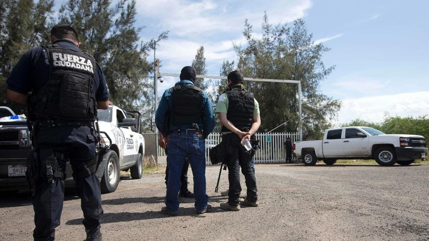 Mexican state police stand guard at the entrance of Rancho del Sol, near Vista Hermosa, Mexico, Friday, May 22, 2015. About 40 people were killed Friday in what authorities described as a large-scale shootout between law enforcement and criminal suspects. Almost all the dead were suspected criminals, said a Federal Police official. The confrontation, which occurred near the border of Michoacan and Jalisco states, started when federal police officers tried to pull over a truck on the highway near the ranch. (AP Photo/Refugio Ruiz)