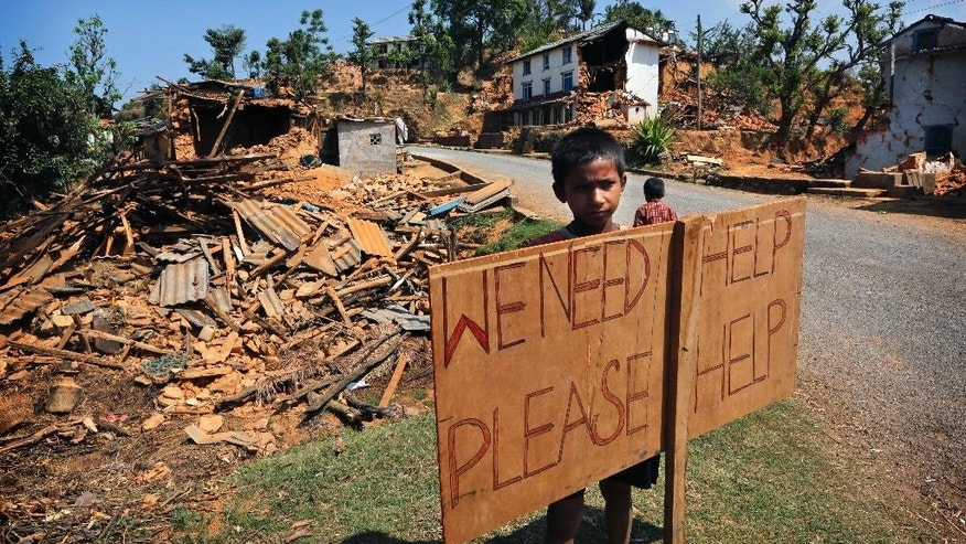 In this Saturday, May 2, 2015 file photo, a Nepalese boy stands outside his village with a signboard asking for help in Pauwathok village, Sindhupalchok district, Nepal. Geologists were sent to earthquake-damaged mountain villages in Nepal this week to assess landslide risks before the rainy season begins next month, an official said Friday, May 22. They are scheduled to report their findings in Kathmandu next week, and the government would then decide which villages are in danger of landslides and need to be relocated. (AP Photo/Manish Swarup, File)