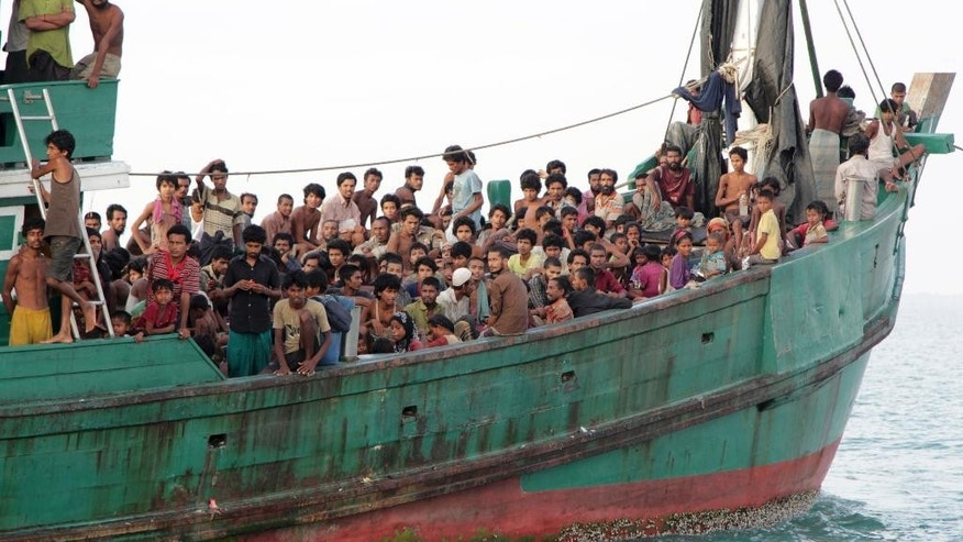 FILE - In this Wednesday, May 20, 2015 file photo, migrants sit on their boat as they wait to be rescued by Acehnese fishermen on the sea off East Aceh, Indonesia. Many of the thousands of migrants abandoned at sea in Southeast Asia this month are Rohingya Muslims who fled their home country of Myanmar. The Rohingya are a Muslim minority in predominantly Buddhist Myanmar, also known as Burma. Numbering around 1.3 million, they are concentrated in western Rakhine state, which neighbors Bangladesh. (AP Photo/S. Yulinnas, File)