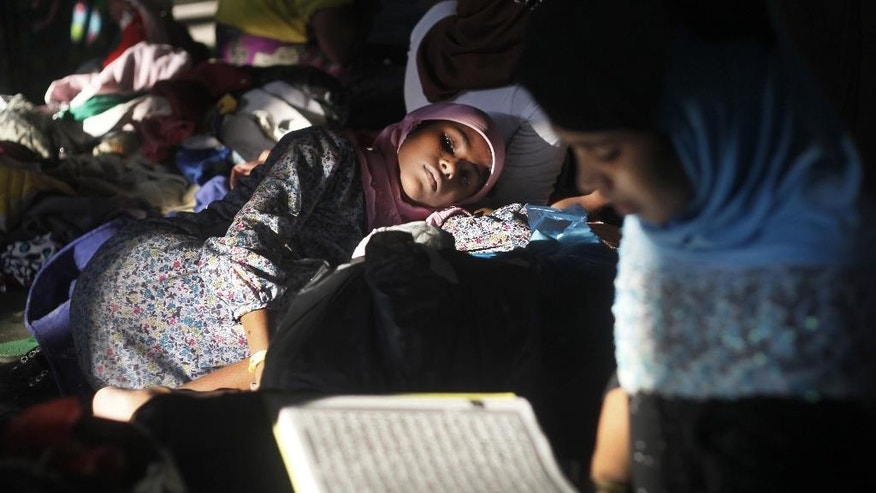 FILE - In this Wednesday, May 13, 2015 file photo, an ethnic Rohingya woman rests on a pile of used clothing donated by local residents as another reads the holy book of Quran at a sports stadium turned into temporary shelter for migrants whose boats washed ashore on Sumatra island on Sunday, in Lhoksukon, Aceh province, Indonesia. Many of the thousands of migrants abandoned at sea in Southeast Asia this month are Rohingya Muslims who fled their home country of Myanmar. With little left for them in Myanmar, the Rohingya have for decades set their sights abroad, most hoping to reach Muslim-majority Malaysia where they can find under-the-table jobs and security. (AP Photo/Binsar Bakkara, File)
