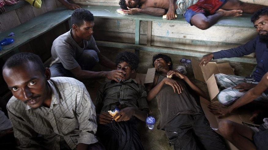 FILE - In this Wednesday, May 20, 2015 file photo, rescued migrants rest as they are given food and drink upon arrival in Simpang Tiga, Aceh province, Indonesia. Many of the thousands of migrants abandoned at sea in Southeast Asia this month are Rohingya Muslims who fled their home country of Myanmar. The Rohingya are a Muslim minority in predominantly Buddhist Myanmar, also known as Burma. Numbering around 1.3 million, they are concentrated in western Rakhine state, which neighbors Bangladesh. (AP Photo/Binsar Bakkara, File)