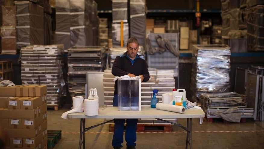 An electoral worker cleans a ballot box to be distributed to a polling station for the upcoming local elections, in Barcelona, Spain, Thursday, May 21, 2015. The Spanish municipal elections will be held on Sunday May 24, to elect members of city councils in Spain. (AP Photo/Emilio Morenatti)