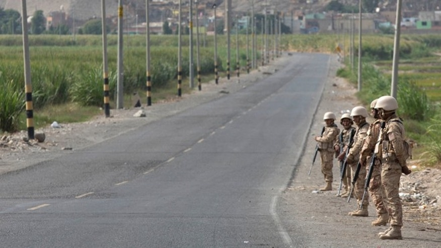 Soldiers stand guard on a highway that was the site of protests yesterday, near Cocachacra, Peru, Friday, May 15, 2015. Residents of this southern coastal valley are opposing the $1.4 billion Tia Maria project of Mexican-owned Southern Peru Copper because they fear the project would contaminate their crops. The protests that began in March have claimed the lives of two civilians and a police officer. (AP Photo/Martin Mejia)
