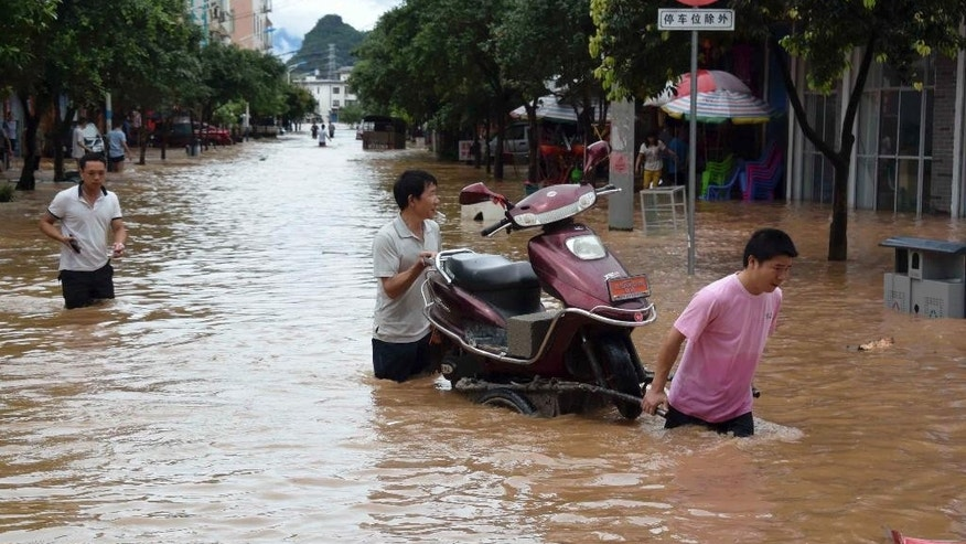 In this Thursday, May 21, 2015 photo released by China's Xinhua News Agency, residents move a motorcycle on a flooded street in Jiahui town of Gongcheng Yao Autonomous County, southwest China's Guangxi Zhuang Autonomous Region. The death toll in China's latest round of flooding has risen to more than 50, including two schoolchildren aboard a bus carrying more than twice its authorized passenger load that plunged into a pond, authorities said Saturday. (Zhou Hua/Xinhua via AP) NO SALES