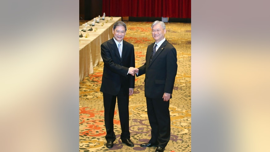 China's Taiwan Affairs Office director Zhang Zhijun, left, and his counterpart Minister Andrew Hsia of the Taiwan's Mainland Affairs Council shake hands in front of the media as they arrive for the start of a two-day cross-strait meeting, Saturday, May 23, 2015, on the outlying island of Kinmen, Taiwan. Zhang is meeting with Hsia to discuss various cross-strait issues, including Taiwan's interest in joining China-led Asian Infrastructure Investment Bank (AIIB) and the latest trade agreements between both sides. (AP Photo) TAIWAN OUT