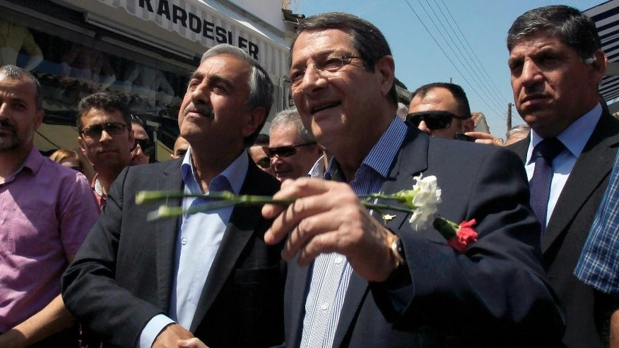 Cyprus President Nicos Anastasiades, right, and Turkish Cypriot leader Mustafa Akinci, shake hands as they walk at a main shopping street at the breakaway northern part of the Cypriot divided capital Nicosia on Saturday, May 23, 2015. Cyprus' rival Greek and Turkish Cypriot leaders took a stroll together on both sides of the divided capital's medieval center to raise the feel-good factor as talks aimed at reunifying the ethnically split island kick into gear. It's the first time that the leaders have done so together since the east Mediterranean island was split in 1974 when Turkey invaded after coup by supporters of union with Greece. (AP Photo/Petros Karadjias)